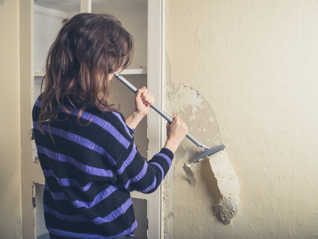 stripping: A young woman is renovating a house and is stripping off the wallpaper with a scraper