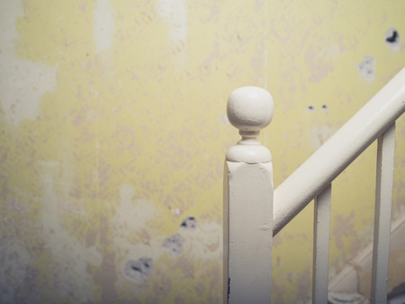 victorian house: A banister and post in an old victorian house with a chipped wall in the background
