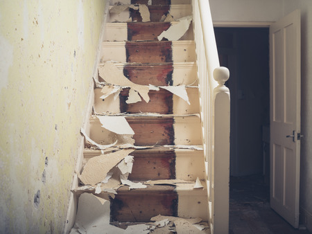 victorian house: An old staircase in a victorian house with pieces of wallpaper and plaster on it