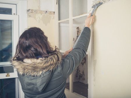 house coat: A young woman wearing a warm winter coat is renovating a house and is stripping off the wallpaper Stock Photo