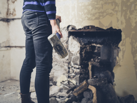 victorian house: A young woman is opening up an old fireplace in a Victorian house with a sledge hammer
