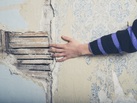 A young female hand is touching an old exposed lath wall Stok Fotoğraf