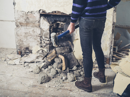 victorian fireplace: A young woman is opening up an old fireplace in a Victorian house with a sledge hammer