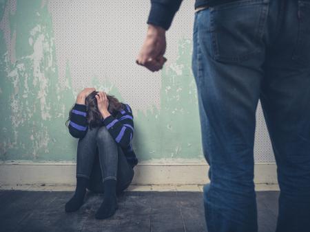 violencia intrafamiliar: Una mujer joven está sentado en el suelo mientras su compañero le ataca Foto de archivo