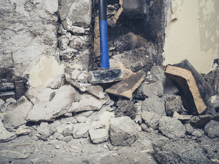 home destruction: A demolished fireplace with a sledge hammer resting against it