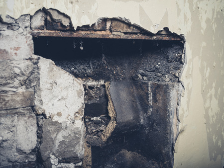 victorian fireplace: A partially demolished victorian fireplace with the remains of the fireback showing Stock Photo