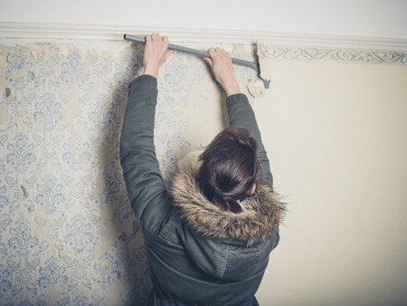 house coat: A young woman wearing a warm winter coat is stripping wallpaper in an old house Stock Photo
