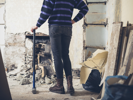 sledge hammer: A young woman is standing by a fireplace with a sledge hammer