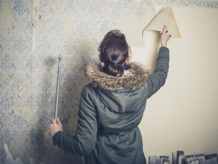 stripping: A young woman wearing a warm winter coat is stripping wallpaper in an old house Stock Photo