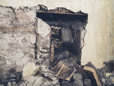A partially demolished victorian fireplace with the remains of the fireback showing Stock Photo