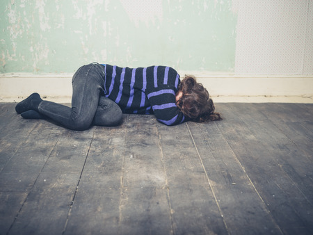 sad lady: A sad young woman is lying on the floor in an empty room Stock Photo