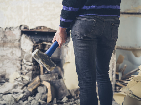 sledge hammer: A young woman is opening up an old fireplace in a Victorian house with a sledge hammer
