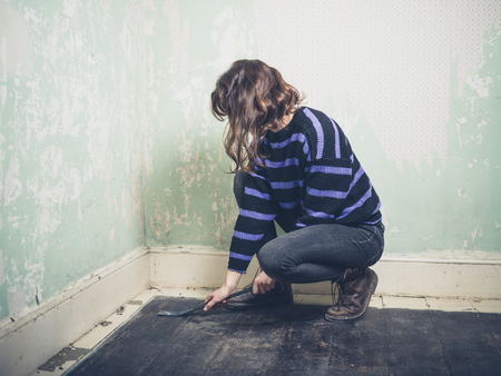prying: A young woman is prying the nails in her floorboards with a crowbar