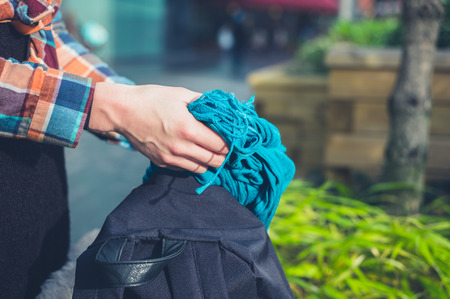 rucksack ': The hands of a young woman is opening a rucksack outside and getting a scarf out of it