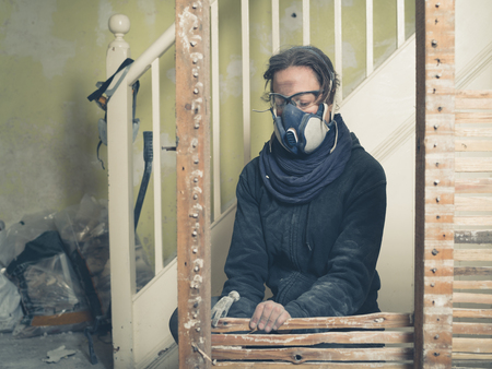 daub: A young woman wearing protective goggles and a dust mask is using a hammer to demolish an old wattle and daub wall