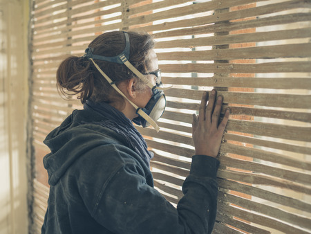 protective workwear: A young woman wearing protective workwear is peeping through an old wattle and daub wall Stock Photo