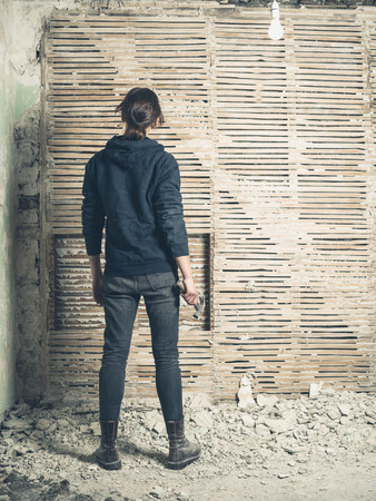 daub: A young woman holding a hammer is standing by an old wattle and daub wall Stock Photo