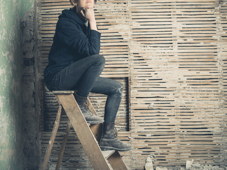 stepladder: A thoughtful young woman is sitting on a stepladder by an old wattle and daub wall