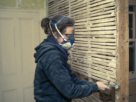 daub: A young woman is repairing an old wattle and daub wall Stock Photo