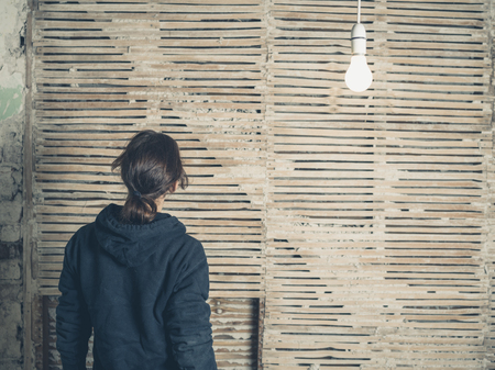 daub: A young woman is standing under a light bulb by an old wattle and daub wall