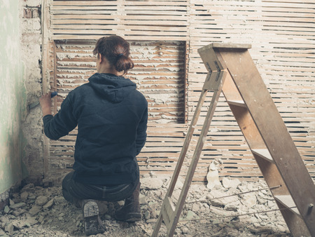 daub: A young woman is chipping off the plaster on a wattle and daub wall with a hammer Stock Photo