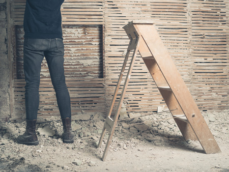 A person is standing by an old wattle and daub wall with a stepladder