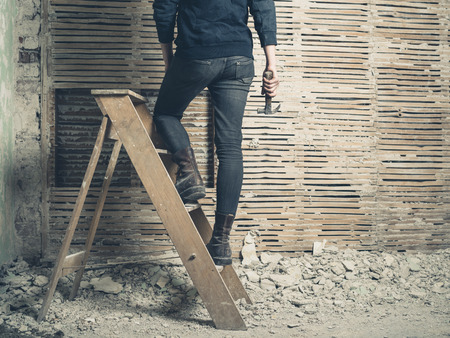 daub: A young woman is standing on a stepladder by an old wattle and daub wall
