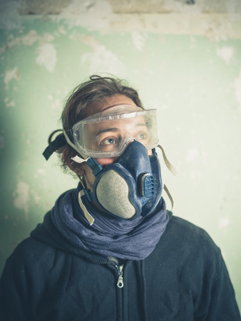 derelict: A young woman is wearing a dust mask and protective goggles is standing in a derelict room undergoing renovations