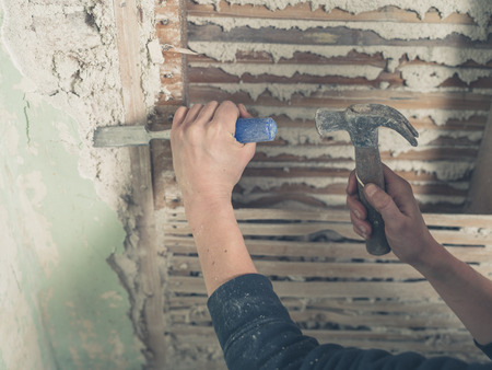 daub: Close up on the hands of a person using a hammer to remove the plaster from an old wattle and daub wall