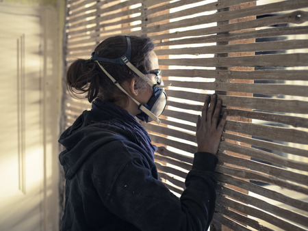 daub: A young woman wearing protective workwear is peeping through an old wattle and daub wall Stock Photo