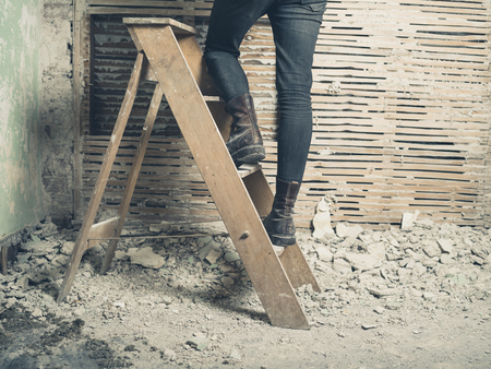 stepladder: A young woman is standing on a stepladder by an old wattle and daub wall