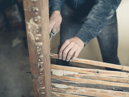 daub: A person is using a hammer to pull out nails from an old wattle and daub wall Stock Photo
