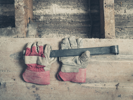 crowbar: A pair of builders gloves and a crowbar on a wooden floor Stock Photo