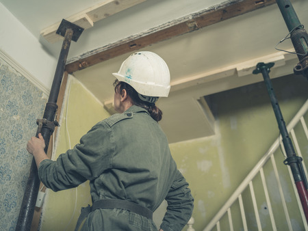 boiler suit: A young woman wearing a hard hat and a boiler suit is inspecting some acro props supporting the ceiling in a house