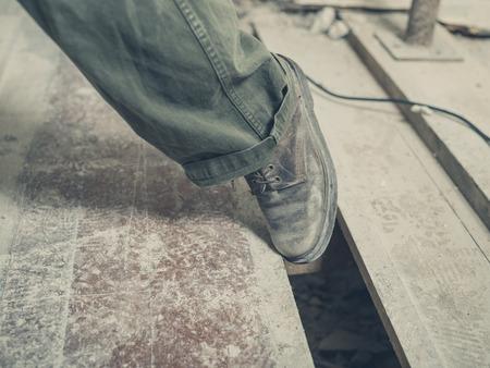 改装部屋の床板間ギャップにつまずく人の足