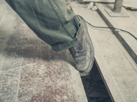 The foot of a person tripping on a gap between the floor boards in a room undergoing renovations Stockfoto