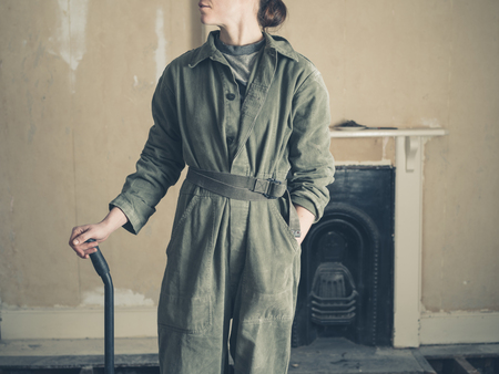 boiler suit: A young woman wearing a boiler suit is standing by a fireplace in a Victorian house with a crowbar in her hand