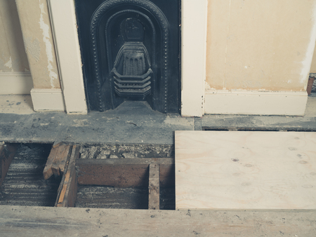 housebuilding: A Victorian room with a fireplace and exposed floor joists after the floor boards have been taken up