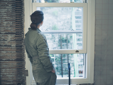 boiler suit: A young woman wearing a boiler suit is standing by the window and is day dreaming Stock Photo