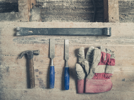 crowbar: A pair of workman gloves a crowbar two chisels and a hammer on a wooden floor