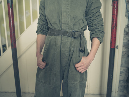 boiler suit: A person wearing a boiler suit is standing in a room that is undergoing renovations Stock Photo