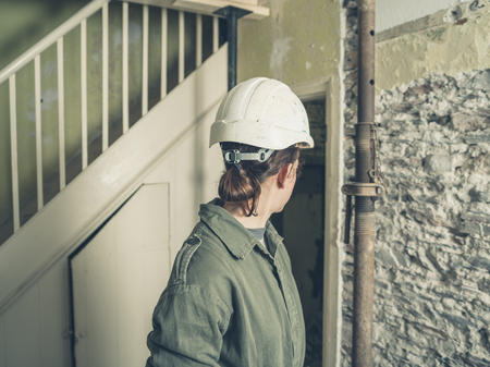 boiler suit: A young woman wearing a hard hat and a boiler suit is standing in a house that is undergoing renovations