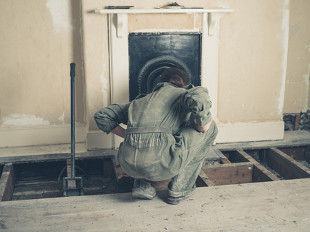 boiler suit: A young woman wearing a boiler suit is examining a fireplace in a Victorian house Stock Photo