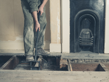 boiler suit: A young woman wearing a boiler suit is taken up the floor boards in a Victorian house Stock Photo