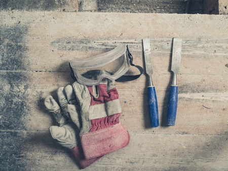 protective goggles: A pair of workman gloves two chisels and a pair of protective goggles on a wooden floor Stock Photo