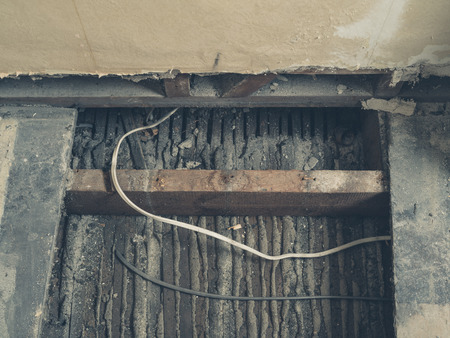 Cables running under the floor boards in a room that is being renovated