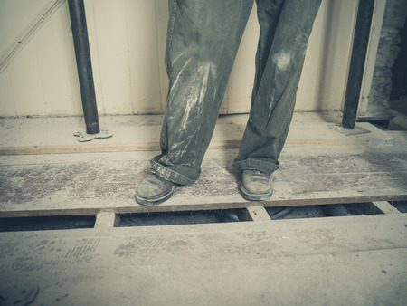 boiler suit: The feet and legs of a person wearing a boiler suit in a room that is underoing renovations
