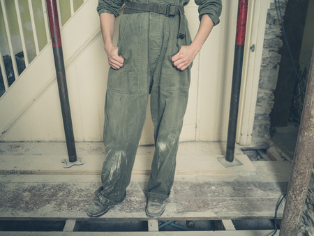 boiler suit: A young person wearing a boiler suit is standing in a house undergoing renovations