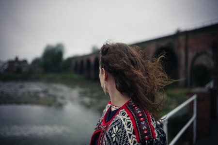 Una mujer joven está de pie por sí sola en un puente en un día frío y sombrío