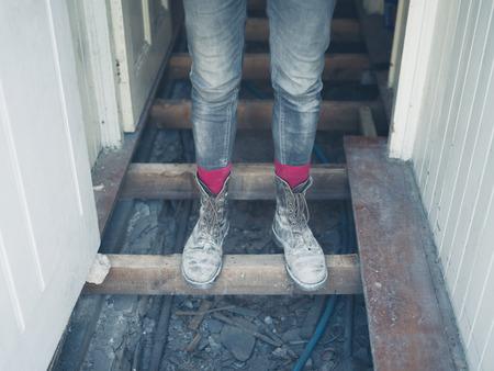 pieds sales: Les pieds d'un travailleur portant vieilles bottes sales debout sur les solives de plancher dans une maison en cours de r�novation